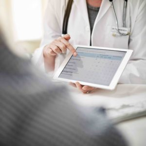 Shot of a doctor showing a senior patient some information on a digital tablet in her office